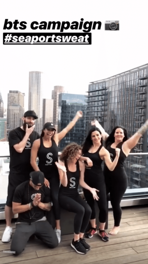 The crew from Sea Sports Sweat all wear blank tank tops and smile as they pose on a rooftop.
