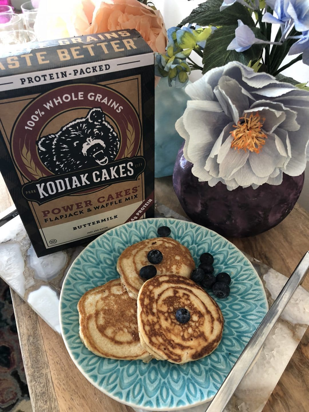 A stack of three blueberry pancakes sits on a teal plate with a box of Kodiak power cakes mix and a vase of flowers on the table.