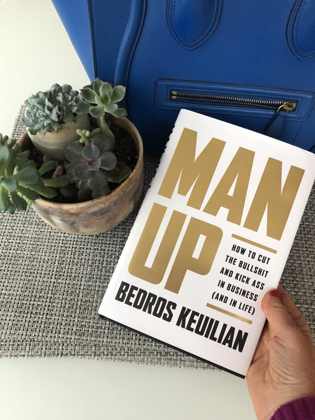 """Sue B Zimmerman holds the book """"Man Up"""" by Bedros Keuilian."""