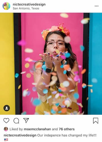 Nicte's blows a handful of confetti at the camera as she poses against a colorful backdrop.
