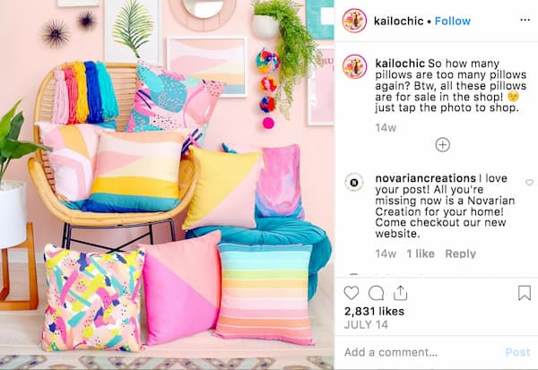 Multi-colored pillows and colorful home accessories are arranged in a light pink room.