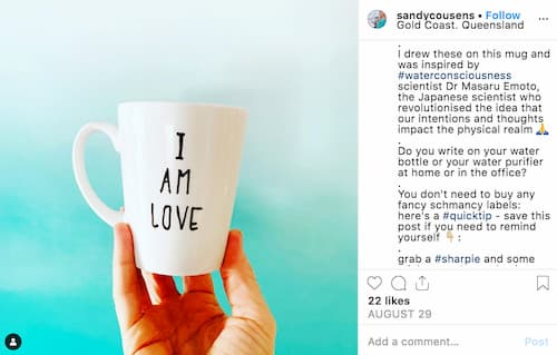 Sandy holds a white mug that says 'I am love' in black writing.