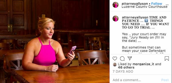 Allyson wearing a bright pink sleeveless dress sits behind a courtroom bench and holds her phone in her hand.