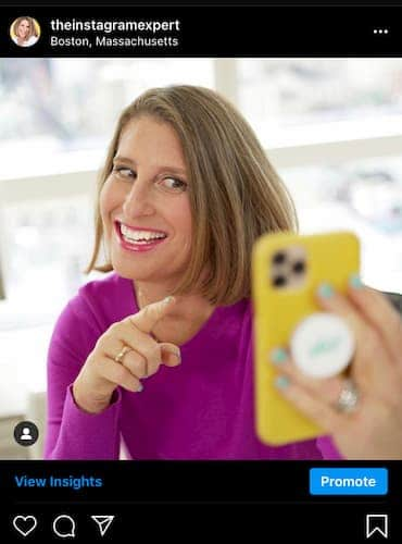 An Instagram post from Sue B Zimmerman that shows her smiling as she looks into her phone and points to the screen.