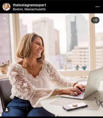 An Instagram post that shows Sue B Zimmerman sitting at her table in a white blouse and blue skirt as she smiles confidently at her computer.