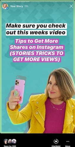 Sue B Zimmerman takes a selfie as she holds a cellphone in a pink case on a teal background.