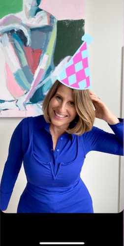 Sue B Zimmerman poses and smiles in a blue dress with a checkered party hat sticker placed on her head.