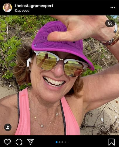 Sue B Zimmerman wears a purple baseball cap and pink tank top as she smiles and waves in her selfie.