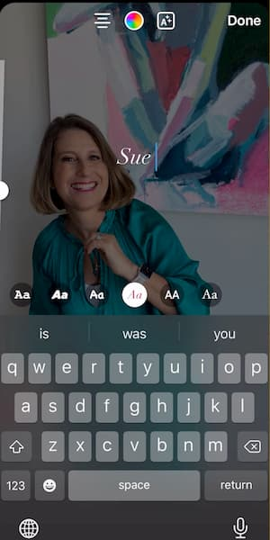 Sue B Zimmerman shares an Instagram Story that shows her smiling and wearing a teal blouse in front of a colorful painting with text that says Sue overlapping it.