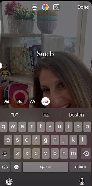 Sue B Zimmerman shares an Instagram Story of her smiling in front of her stylized bookcase.