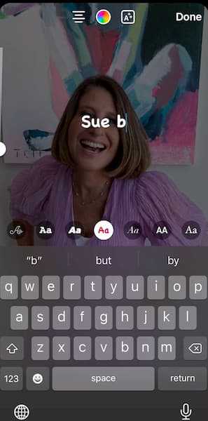 Sue B Zimmerman shares an Instagram Story with her wearing a pink top in front of a colorful painting with the text Sue B over it.