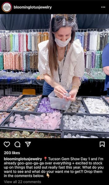 Jenn, owner of Lotus Jewelry, sorts through pink crystals at a craft show.