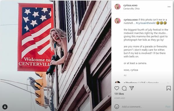Cyrissa in her Instagram post as she smiles and leans out the window with an American flag banner behind her.